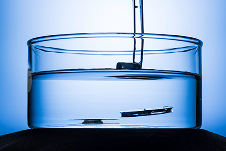two metallic structures submerged in water, one floating to the surface after a weight placed on top if it has been removed.