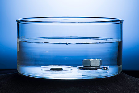 two metal discs submerged in water, one weighted down by a metal washer and nut