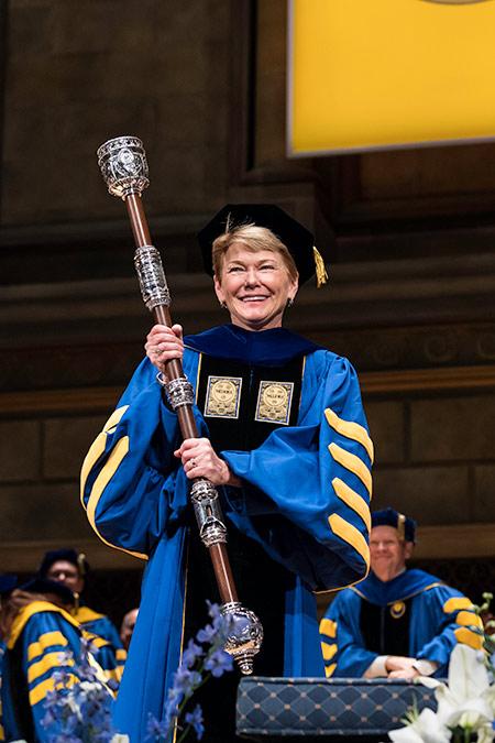 President Sarah Mangelsdorf in academic regalia holding the mace.