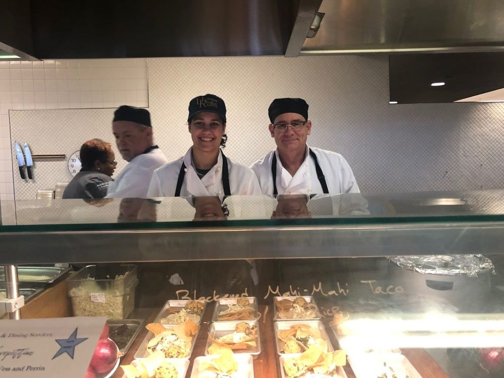 two public safety officers in chef uniforms smile from behind kitchen counter.