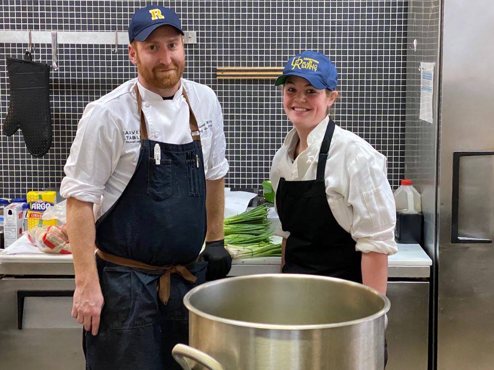 Two people in chef uniforms smile from behind a large pot of boiling water.