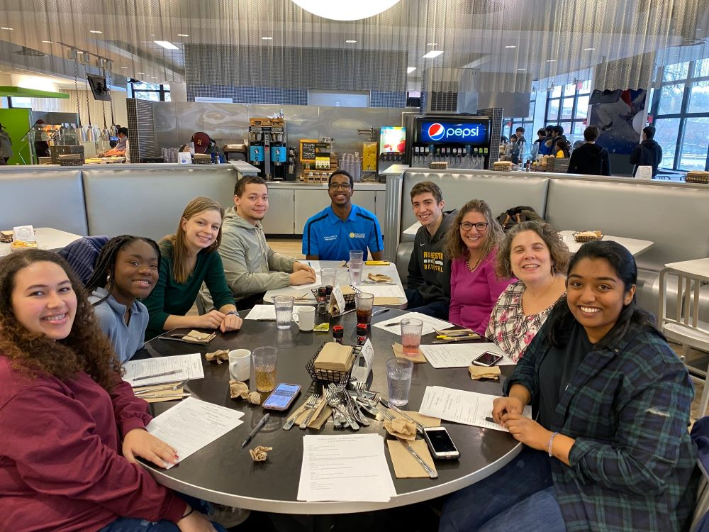 large group of students and staff smile as they sit around a table in Danforth Dining Center.