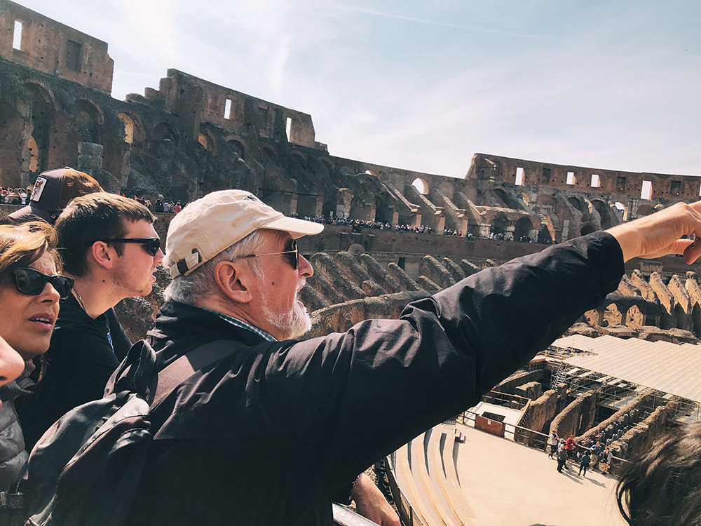 a professor points to something inside the Roman Colosseum
