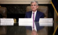 Jerome Powell sits at a conference table filled with name plates for other Fed governors.