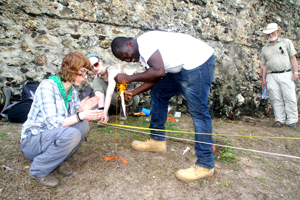 students putting markers in the ground outside an ancient fort.