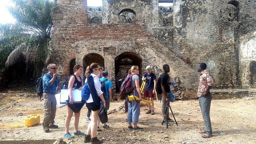 group of students gather outside a fort