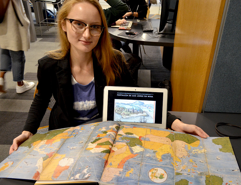 students holds a large map of the world and a tablet computer.