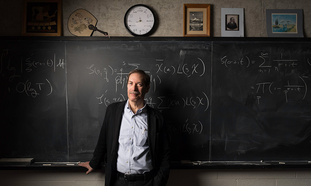Steve Gonek in front of blackboard with mathematical formula.