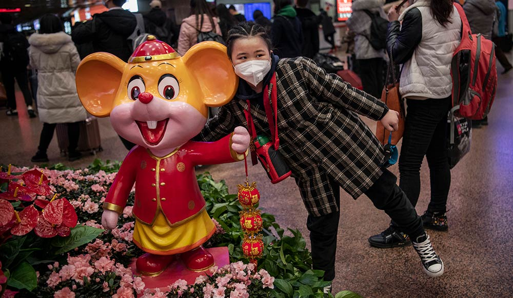 Chinese girl wearing a face mask poses for a photo with a year of the rat cartoon mascot in a busy train station.