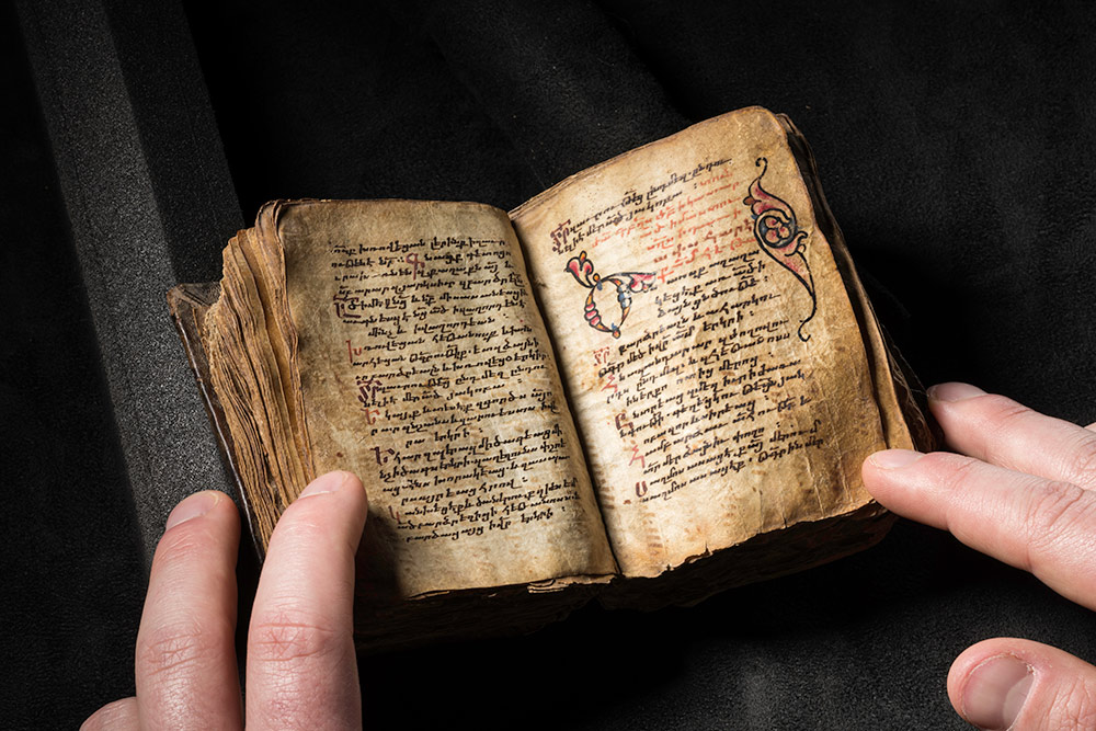 small ancient book, with someone's fingers holding it open to a handwritten page