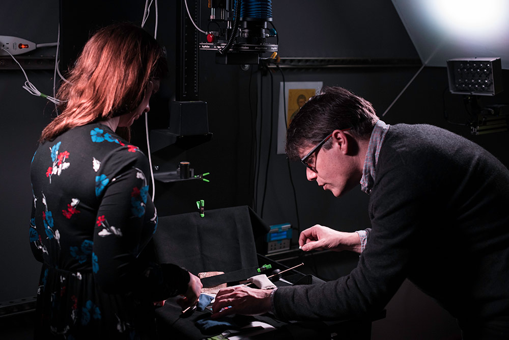 two researchers lean over a scanner in a multispectral imaging lab