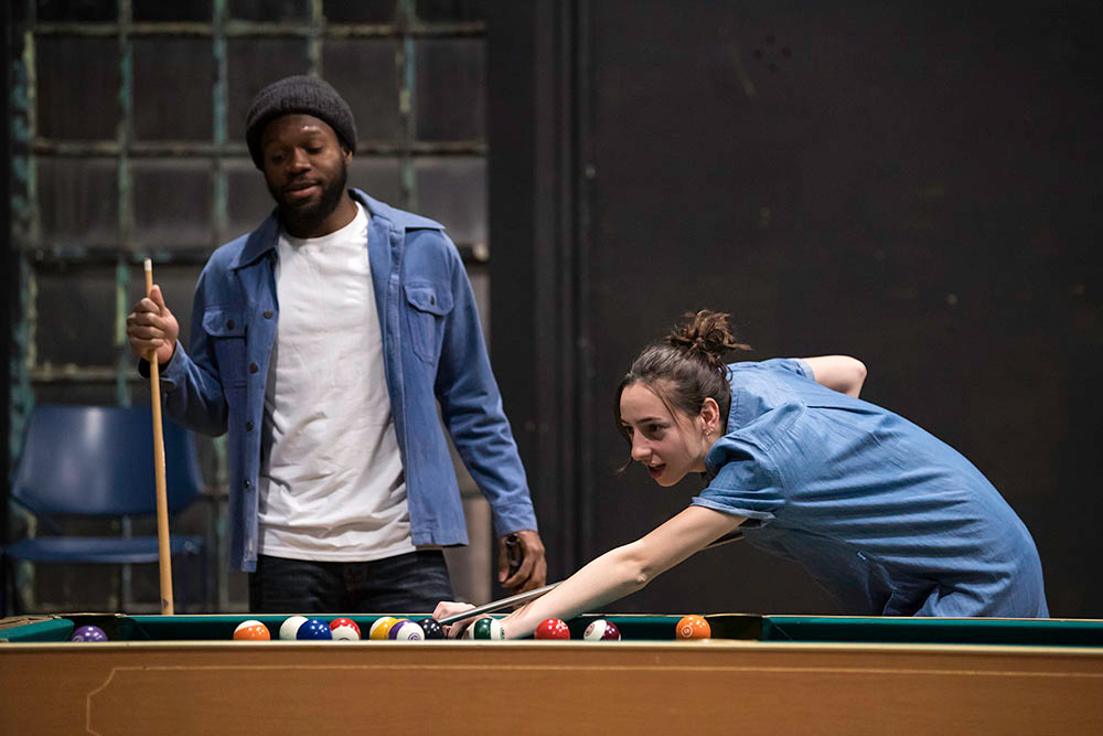 two actors on stage, playing pool.