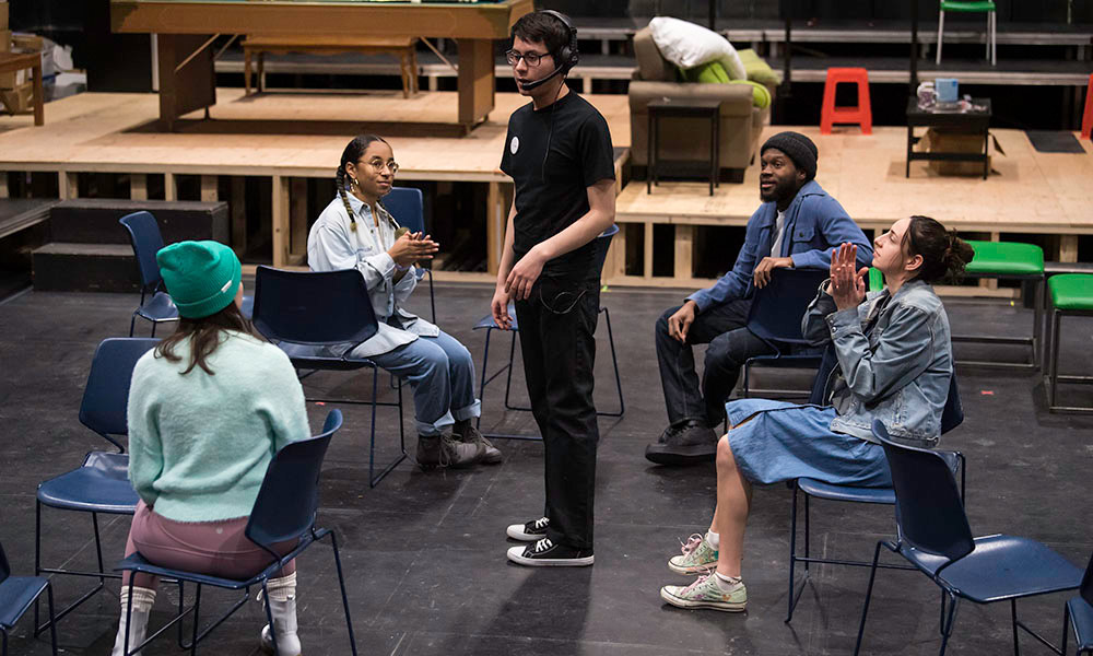 four actors sitting on chairs on stage listening to a director.