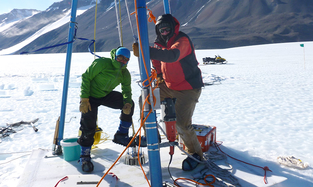 two scientists pose at ice drill in Antarctica.