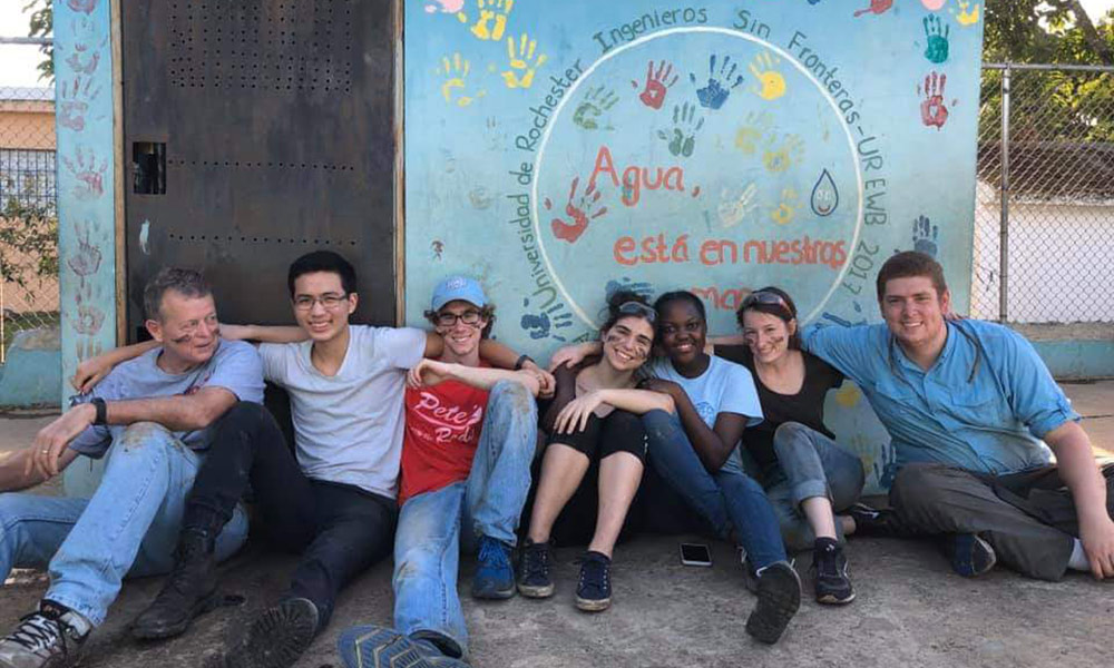 group portrait of students leaning against a school wall painted with children's handprints.