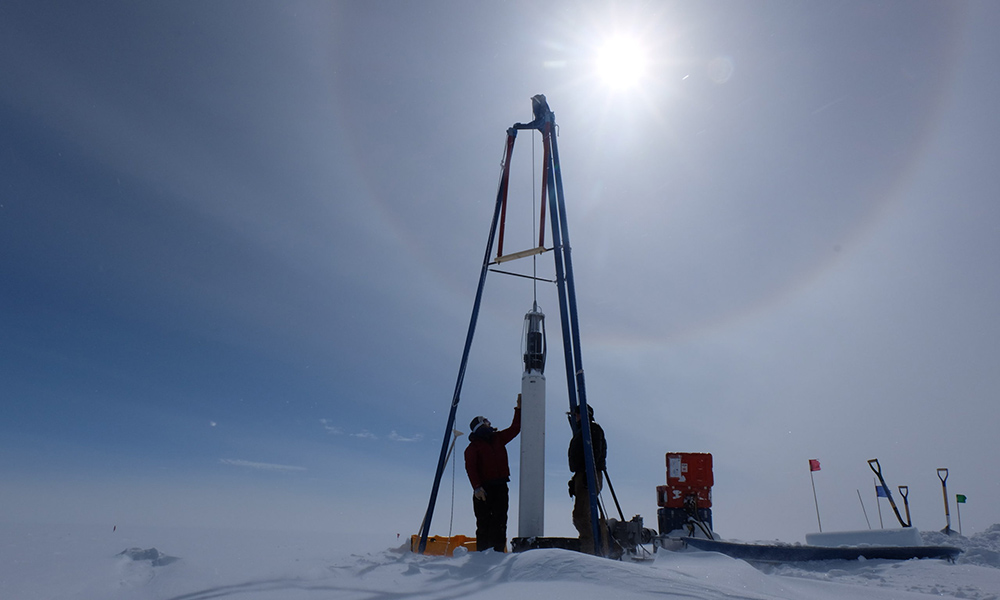 two researchers at a ice core drill in Greenland.