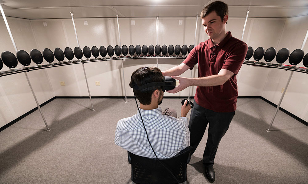 person sitting, wearing a virtual reality headset, and surrounded by a circle of audio speakers