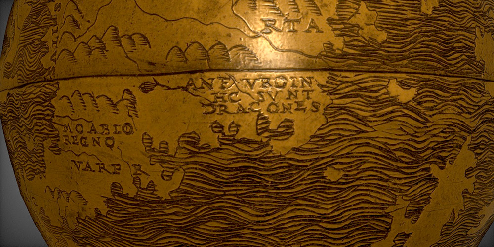 close up detail of a wooden globe with the words Hic Sunt Dracones.