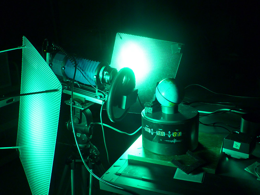 small globe sits on a stand which being scanned by a bright green light.