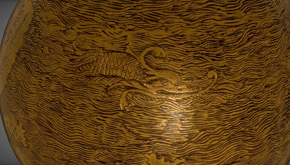 close-up detail of a sea monster carved onto a wooden globe.