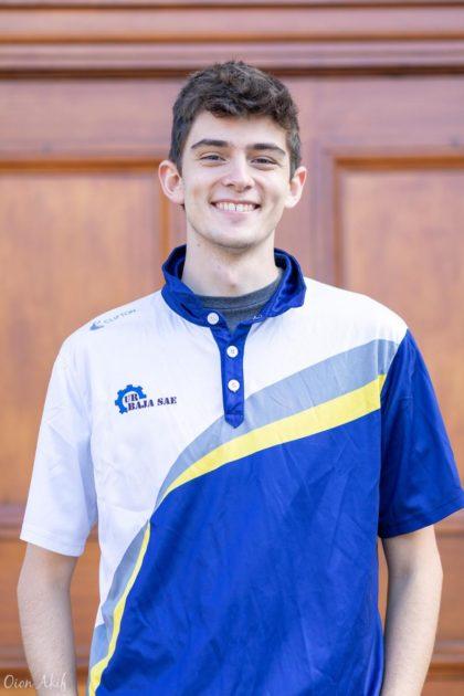 Ethan Fahnestock smiling, in UR SAE Baja team polo shirt.
