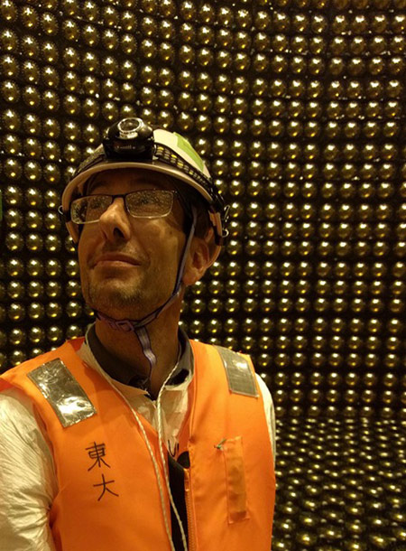 professor in a hard hat and safety vest stands in a large detector array.