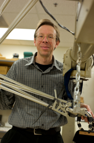 Randal Nelson poses with a robotic arm.