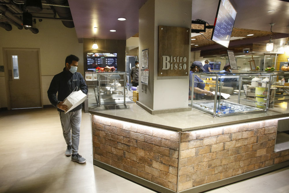 Heri Rajaoberison '22 carries a to-go bag to pick up lunch at the Bistro 1850 serving station.