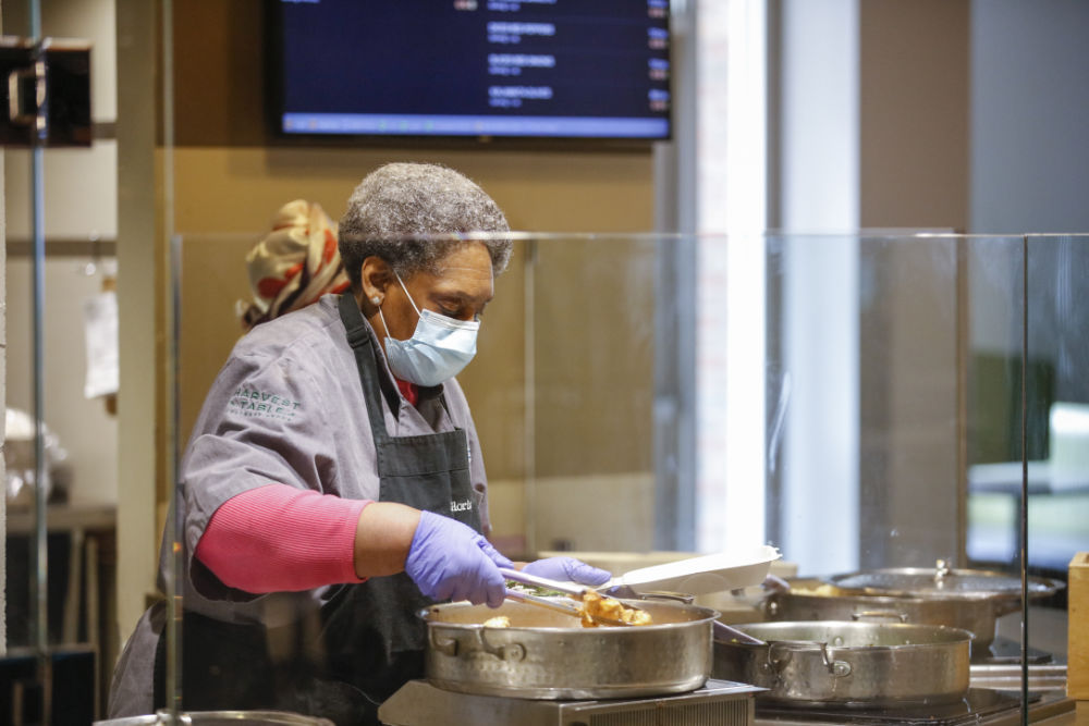 Gloria Jackson wears a face mask and uses cooking tongs to fill a to-go lunch container.