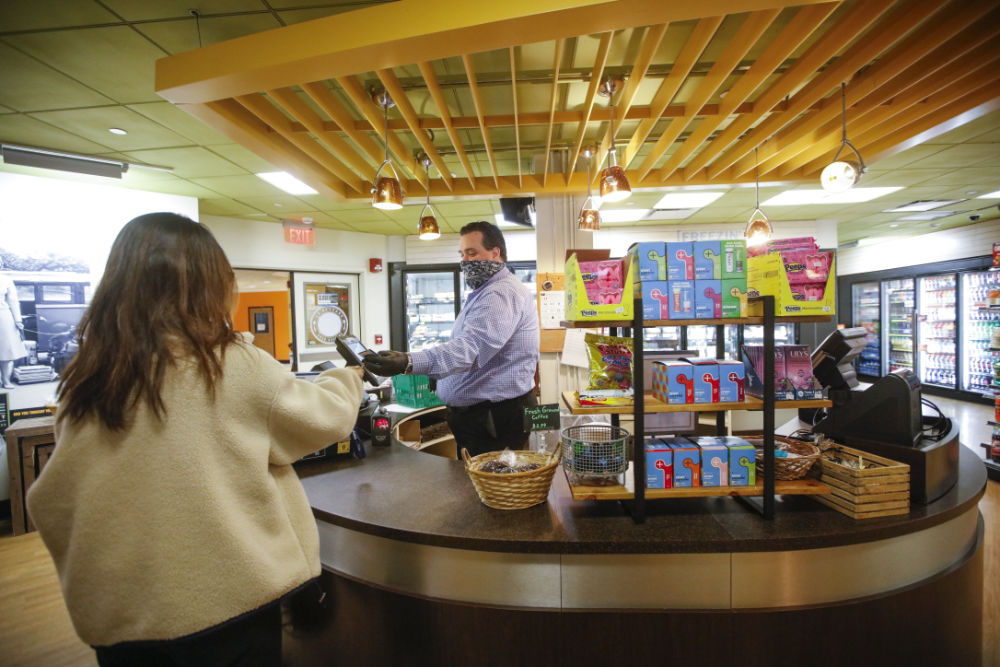 Brant Lewis, donning a face mask, cashes out a student, seen from behind, at Hillside Market.