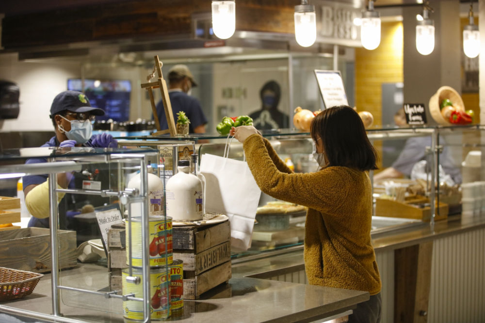 Amy Wang holds a white to-go lunch bag at one of the serving stations in Douglass Dining Center.