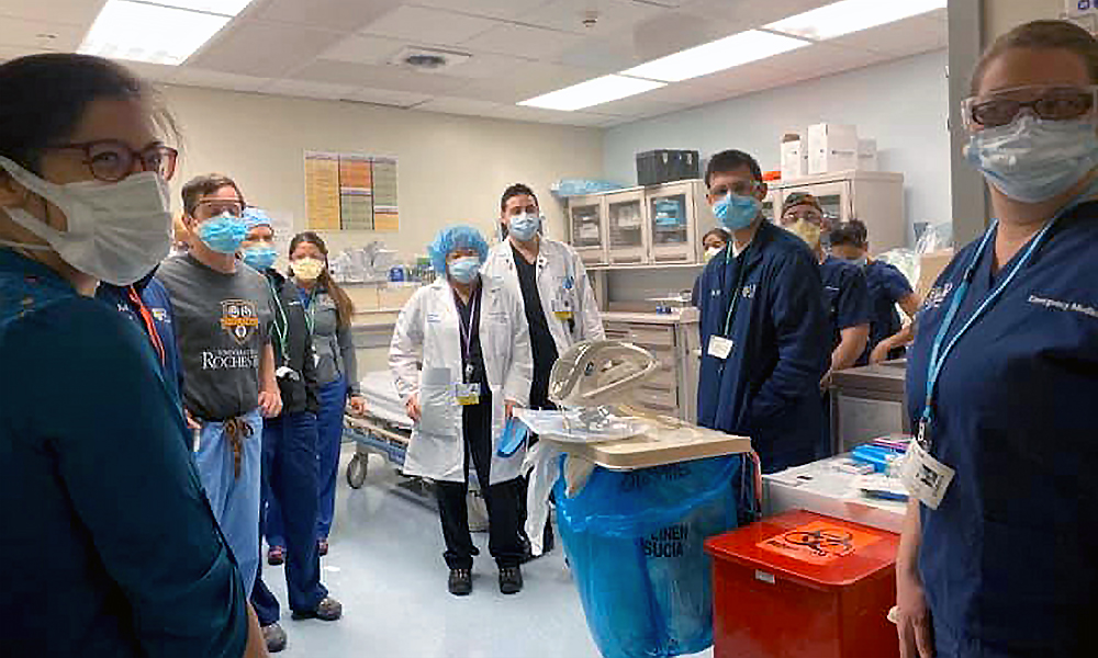 team of doctors and nurses in scrubs and masks.