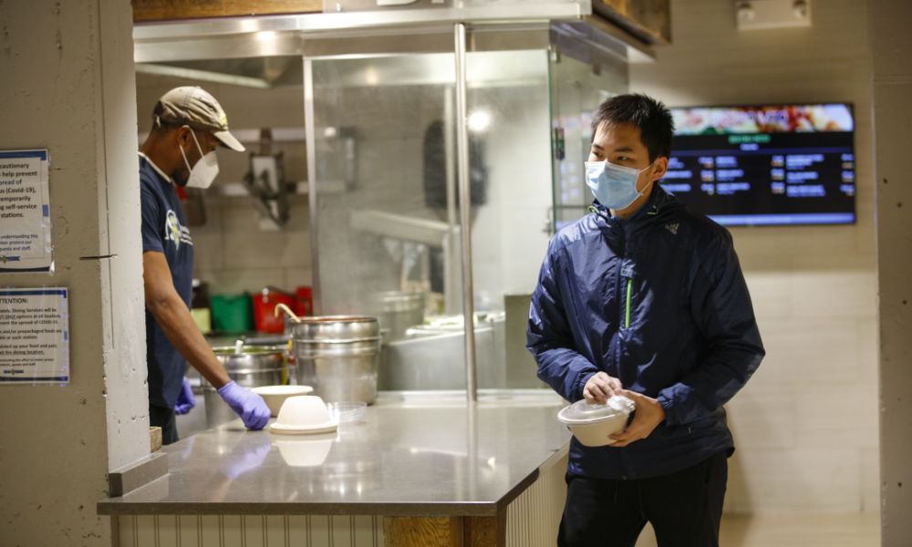 student wearing mask walks through dining services holding bowl of take-out