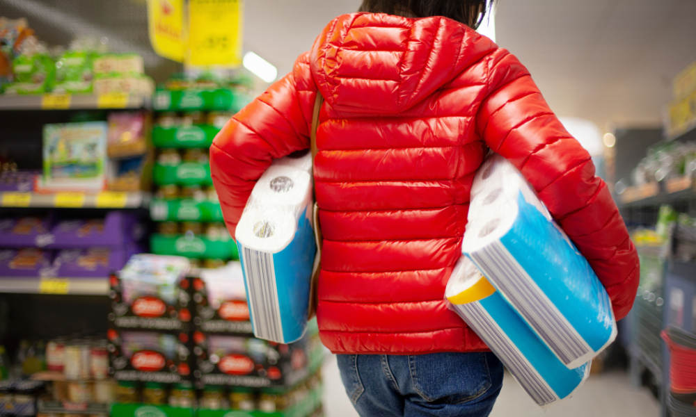 Woman at supermarket carries three large packages of toilet paper
