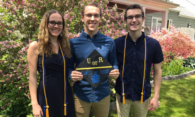triplets in commencement regalia pose and hold mortarboards outside their home.