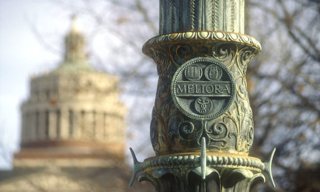 "Flagpole with ""Meliora"" inscription on the Eastman Quad with Ruh Rhees Library in the background."
