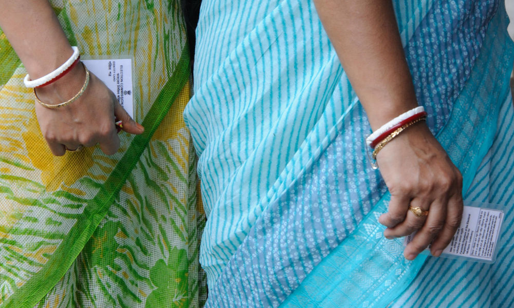 Close up of the bodies and arms of two women in saris wearing bracelets and holding electoral commission identity cards.