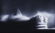 Ghostly photo of icebergs in fog at night.