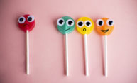 Four lollipops with cartoon eyes and facial expressions on pink background.