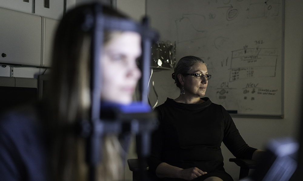 Woman's face framed by visual training device, with researcher Huxlin in background.