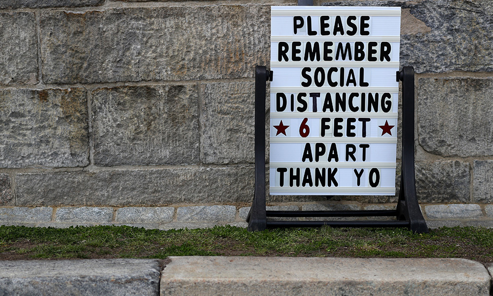Sign posted outside a business reads PLEASE REMEMBER SOCIAL DISTANCING 6 FEET APART THANK YOU.