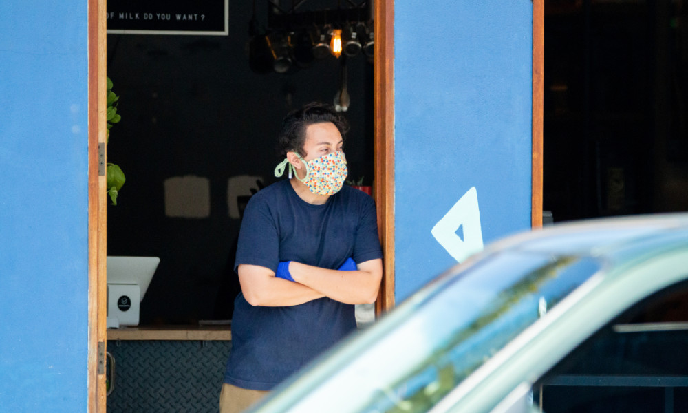 Man wearing a face mask stands in the doorway of cafe as customers stay at home.