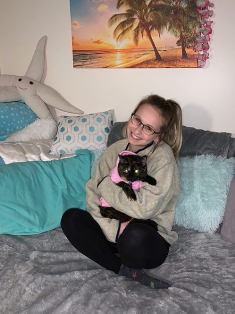Student on bed, holding cat, in dorm room.