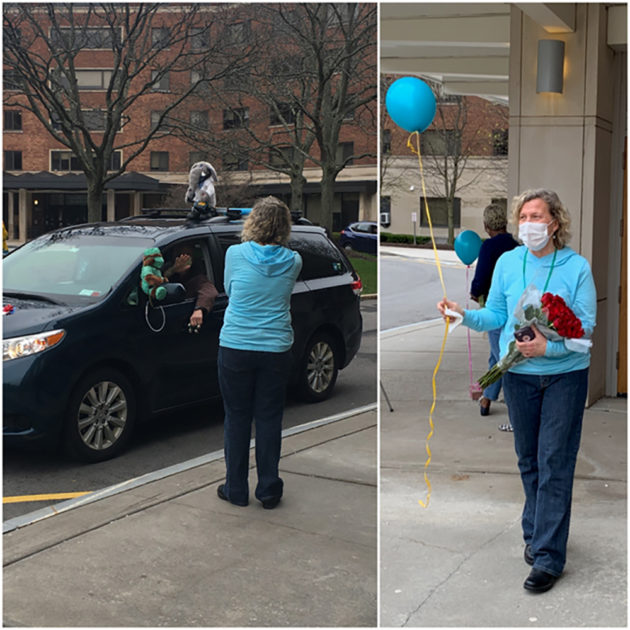 nurse holds a balloon as cars drive past the UHS building.