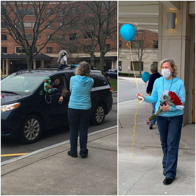 nurse in a mask holds a balloon as cars drive past the UHS building.
