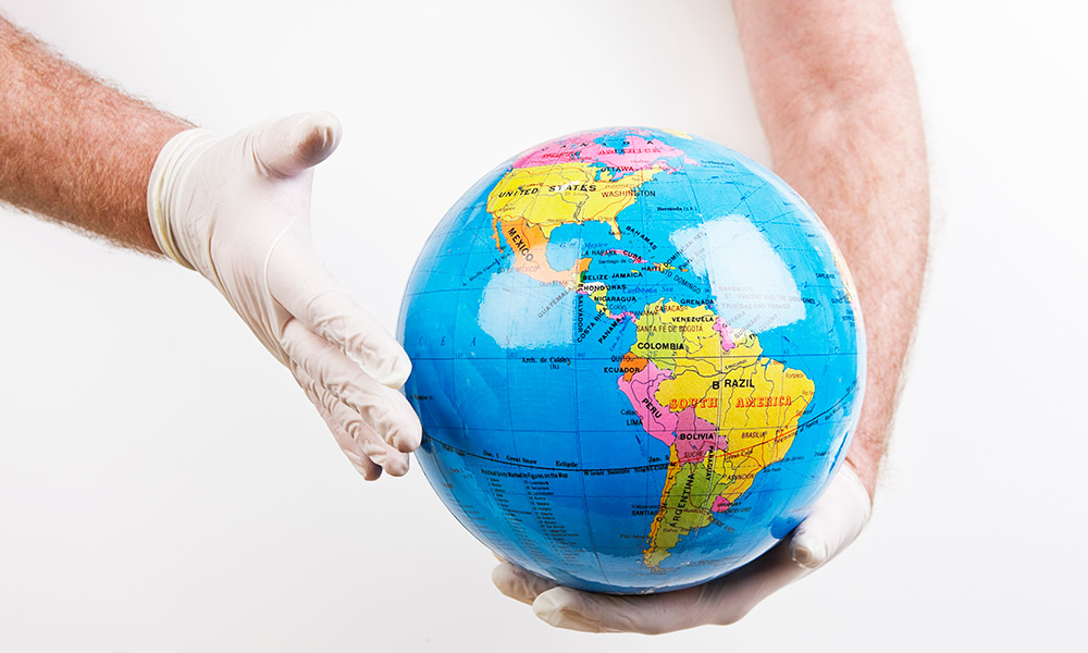 globe held by gloved hands
