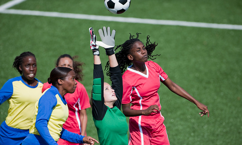 women soccer players vying for the ball