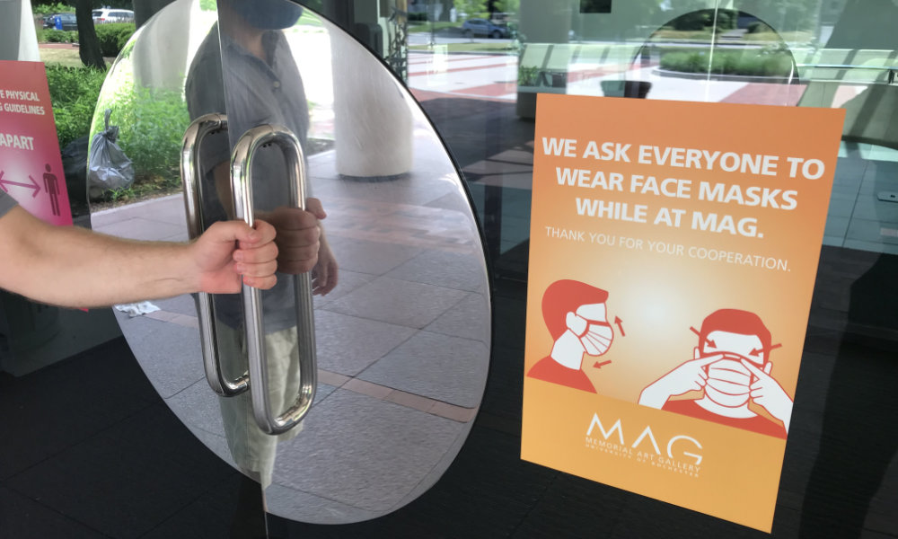 Man's arm opens the doors of the Memorial Art Gallery, which feature a bright orange sign asking everyone to wear a mask while at MAG>