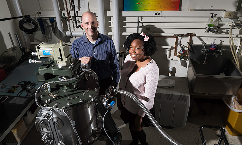 Diarra Bell '20 standing with Craig McMurtry, senior research engineer at the infrared research laboratory, in the lab.