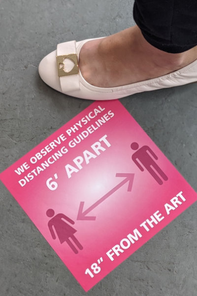 Foot wearing white shoe next to bright pink floor decal at MAG asking people to stay six feet from each other and 18 inches from the art.
